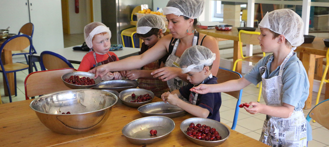 Un groupe d'enfant accompagné d'une animatrice dénoyautent des cerises pour préparer des clafoutis