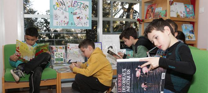Des enfants lisent des livres au coin lecture de la médiathèque de l'Écolothèque
