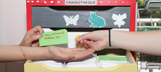 Une graine est echangée de main à main devant les tiroirs de l'armoire de la grainothèque de l'Écolothèque