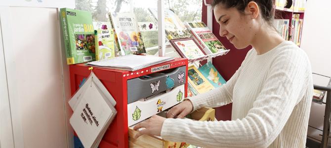Un usager recherche des graines dans un tiroir ouvert de l'armoire de la grainothèque de l'Écolothèque