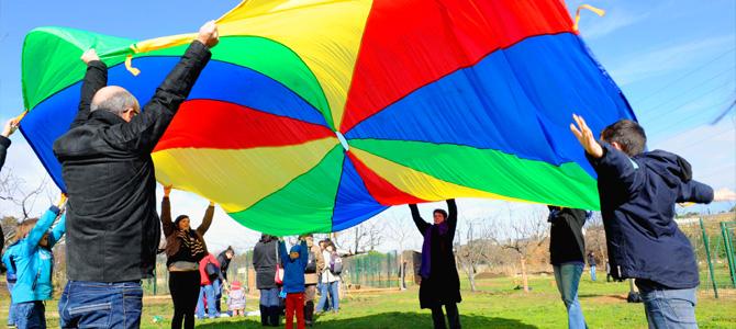 Enfants et adultes jouent en coopérant avec un parachute