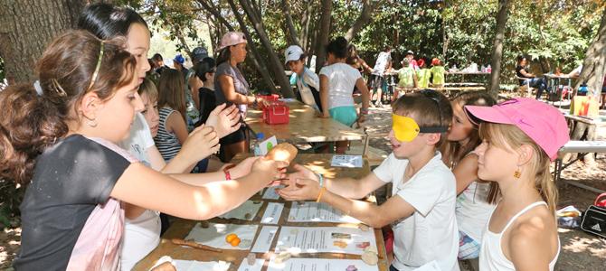Un enfant avec les yeux bandés essaye de reconnaître des fruits et des légumes données par d'autres enfants