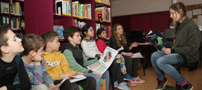 Une animatrice lit une histoire à un groupe d'enfants à la médiathèque de l'Écolothèque