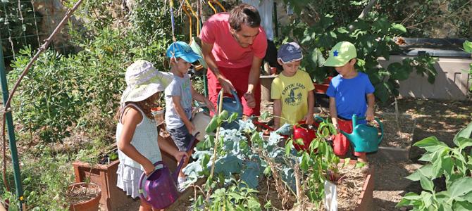 Des enfants accompagnés d'un animateur arrosent les plantations du jardin des maternels de l'Écolothèque