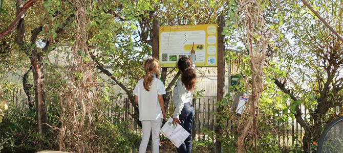 Deux enfants recueillent des informations sur le panneau du sentier agroécolgie du jardin des sens pour remplir la fiche de l'outil pédagogique