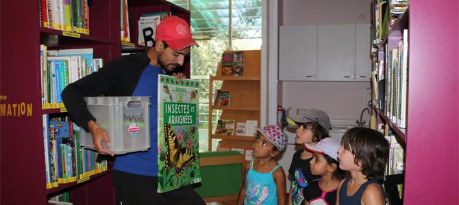 Un animateur présente un livre à un groupe d'enfants dans la médiathèque de l'Écolothèque