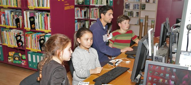 Des enfants accompagnés par un animateur effectuent des recherche internet sur les ordinateurs de la médiathèque de l'Écolothèque