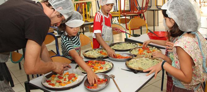 Un groupe d'enfant acompagné d'un animateur préparent des tartes de légumes