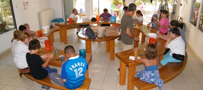 Des enfants et un groupe d'adulte accompagnés d'animateurs font de la vannerie dans une salle de l'Écolothèque