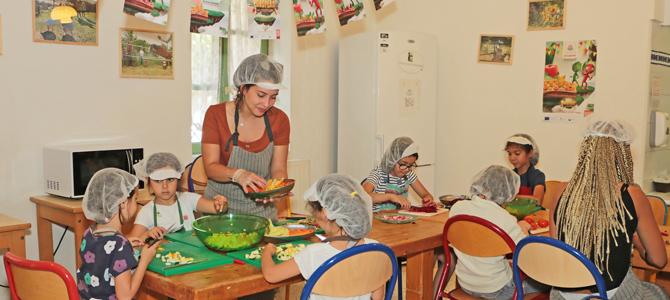 Un groupe d'enfant acompagné de deux animatrices préparent des verrines de légumes du potager de l'Écolothèque