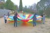 Les participants tiennet une toile de parachute multicolore