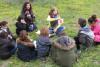 Une intervenante montre une image d'abricot et demande à un groupe d'enfants comment le nommer en anglais
