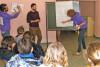 Trois agents expliquent à un groupe d'enfants comment un arbre se nourrit expliquant le rôle des racines