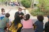 Deux adultes animent un parcours pour 5 enfants de dos sur une table à l'extérieur