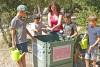 un groupe d'enfants et leur animatrice entretiennent le composteur de jardin