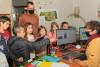 Un groupe d'enfants et leur animateur interrogent la directrice de l'Écolothèque dans son bureau