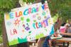 Un panneau réalisé par les enfants en premier plan avec écrit : de la graine à la plante et des enfants floutés en arrière plan