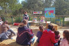 assis sur des ballots de paille, des visiteurs écoutent une animatrice au zoo