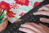 Des main tapent sur un clavier d'ordinateur entouré de crayons de couleur et d'un dessin d'enfant