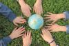 Des mains d'enfants sont autour d'un globe terrestre