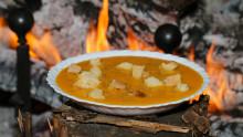 une assiette creuse avec une soupe orangée et des croutons de pain est présentée devant un feu de cheminée allumé