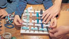 """Des mains d'enfants et d""""adulte en gros plan tendent des morceaux de tissus sur une planche en bois cloutée pour fabriquer un tawashi"""