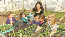 6 enfants et leur animatrice arrosent des semis dans la serre