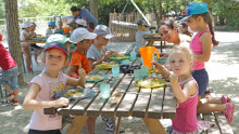 Des enfants mangent leur repas dehors sur une table