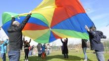 Des adultes et des enfants coopèrent en jouant au jeu du parachute