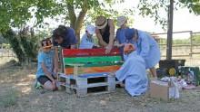 Deux adultes et cinq enfants construisent un banc en palettes
