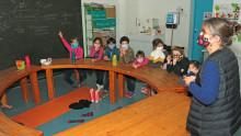Une adulte anime en salle un atelier philo sur la solidarité face à un groupe d'enfants