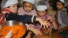 Des enfants équipés de charlottes mélangent des carottes rapées avec d'autres ingrédients pour préparer des cakes aux carottes