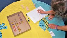 un enfant tente de trouver un mot à partir de lettre trouvées