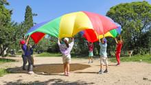 Des enfants jouent au jeu du parachute, une grande toile de couleurs qui est déployée en coopérant