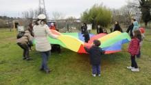 Des parents et des enfants coopèrent en jouant au parachute, une toile tendue colorée tenue par tous