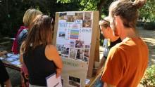 Des agents éducatifs animateur présentent, à l'aide d'un panneau, les projets réalisés durant l'année