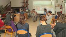 plusieurs personnes assises en rond dans une salle parlent de leur expérience
