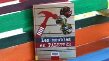 """Livre """"Les meubles en palettes"""" contre une palette peinte multicolore"""