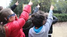 Des enfants équipés de lunettes d'observation pour éclipse solaire pointent un doigt en direction du Soleil