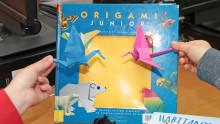 Des mains d'enfants portent des oiseaux en origami devant un livre sur l'origami