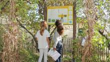 Deux enfants sont devant un panneau dans un jardin