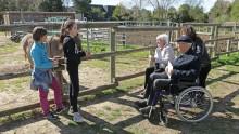 Des enfants explique à des retraités le fonctionnement de la ferme
