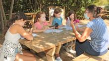 4 jeunes filles interrogent la directrice de l'Accueil de loisirs sur une table de pique-nique