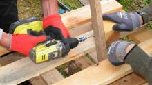 Des mains en gros plan vissent des morceaux de bois