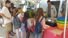 un groupe d'enfants avec leur animateur sont devant le stand d'un maraîcher au marché de Celleneuve