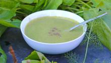 Une assiette creuse contenant de la soupe verte et une cuillere est installée sur une ardoise avec des légumes verts autour