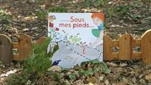 """Livre """"Sous mes pieds"""" posé sur des feuilles mortes contre une petite barrière en bois"""