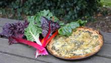 Une tarte aux blettes ainsi qu'un bouquet de blettes sont posés sur une table en bois