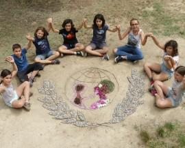 Des enfants se tiennent la main autour du logo de l'Unicef créé en éléments naturels
