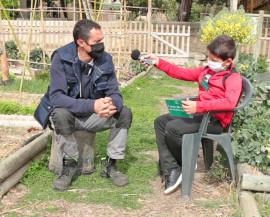 un enfant interview un adulte dans le potager